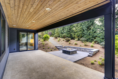 Photo pour New modern home features a backyard with covered patio accented with a wood plank ceiling and a rectangular fire pit, made of concrete and slate tiles. Northwest, USA - image libre de droit