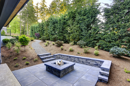 Photo for New modern home features a backyard with rectangular concrete fire pit framed by slate pavers and overlooking the lush garden. Northwest, USA - Royalty Free Image