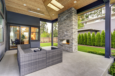 Photo for New modern home features a backyard with covered patio accented with stone fireplace, vaulted ceiling with skylights and furnished with gray wicker sofa placed on concrete floor. Northwest, USA - Royalty Free Image