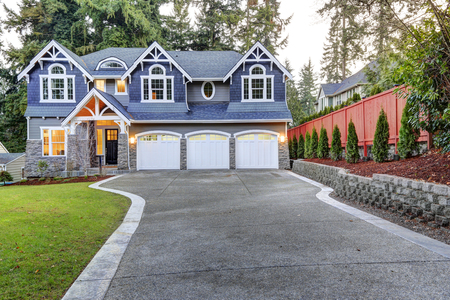 Foto de Luxurious home exterior with blue vinyl siding and white trim. Long concrete driveway lead to three attached garage spaces. Beautiful curb appeal. Northwest, USA - Imagen libre de derechos