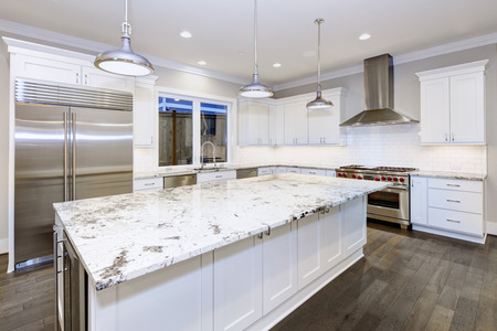 Photo for Large, spacious kitchen design with white kitchen cabinets, white kitchen island with lots of storage, white Granite countertops, subway tiles and stainless steel appliances. Northwest, USA . Northwest, USA - Royalty Free Image