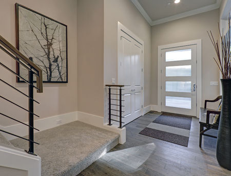 Photo for Bright entryway with creamy walls highlighting modern glass door over gray hardwood floors. Includes white doors built-in closet, wood bench and staircase with horizontal railings. Northwest, USA  - Royalty Free Image