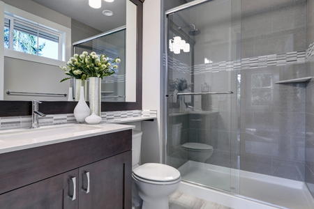 Photo for Bright new bathroom interior with glass walk in shower with grey tile surround, brown vanity cabinet topped with white counter and paired with mosaic tile backsplash. Northwest, USA  - Royalty Free Image