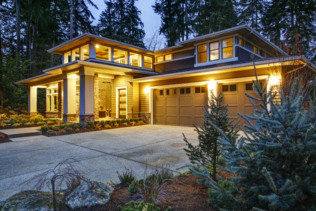 Photo for Luxurious new construction home exterior at sunset. View of two garage spaces with concrete driveway and illuminated porch with columns. Northwest, USA - Royalty Free Image