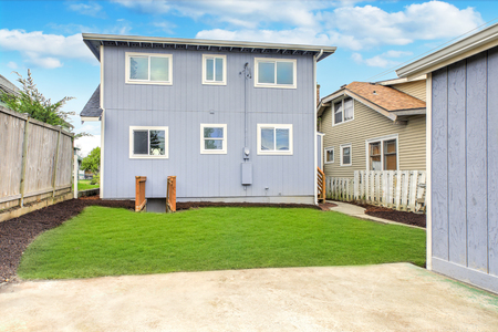 Foto de Blue home exterior with large fully fenced back yard and well kept lawn. - Imagen libre de derechos