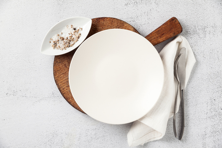 Photo for empty plate and cutlery on a wooden cutting board. a fork, a knife and a salt bowl with a pepper shaker. on white stone background, napkin. the table is set for breakfast or lunch - Royalty Free Image