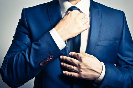 Photo pour Businessman in blue suit tying the necktie - image libre de droit