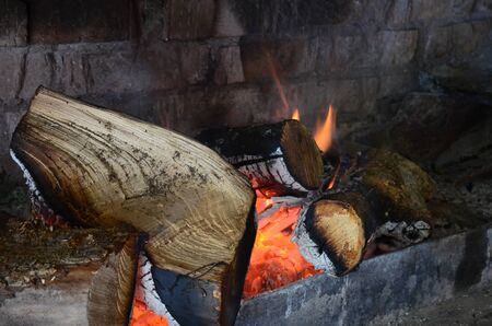 Photo for The hearth by the brickwork with burning wooden logs. Tongues of fire, ash and red-hot wood - Royalty Free Image