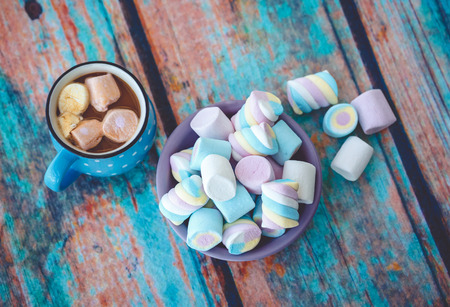 Photo for Different kinds of marshmallow on wooden table and cup of coffee. Photo toned with vignette. - Royalty Free Image