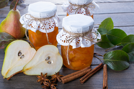 Photo pour Pear jam and fresh pears cinnamon sticks, anise stars and green  leaves on the table. - image libre de droit