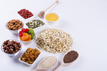 Foto per Ingredients for homemade oatmeal granola. Oat flakes, honey, nuts, dried fruit and seeds. Healthy breakfast concept. - Immagine Royalty Free