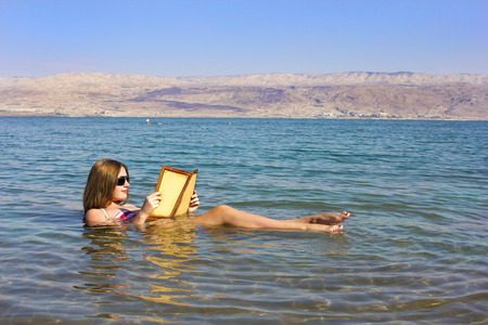 Photo for beautiful young woman reads a book floating in the waters of the Dead Sea in Israel - Royalty Free Image