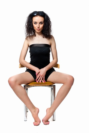 Beautiful girl with long legs sitting on a chair in the studio isolated on a white background