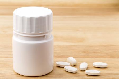 Foto de White pills bottle on wooden table background - Imagen libre de derechos