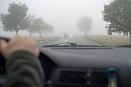 Photo for Car driving in thick fog, seen through windscreen of other vehicle - Royalty Free Image