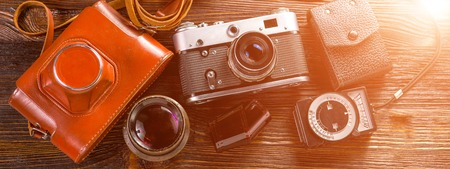 Photo for Old film camera, lenses and old exposure meter on a wooden background. Horizontal photo banner for website header - Royalty Free Image