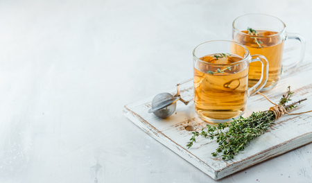 Foto de Transparent glasses cup of herbal tea with thyme and sprigs of thyme tied in a bunch on a white background - Imagen libre de derechos