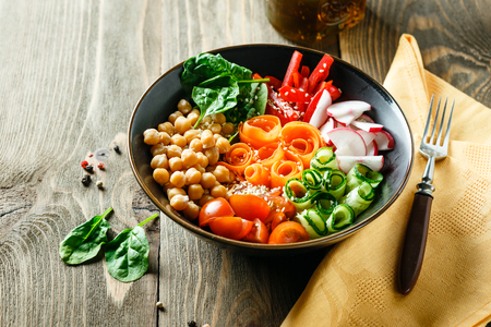 Photo pour Colorful Buddha Bowl with chickpeas, carrots, tomatoes, cucumbers, radish and peppers on a wooden table. Vegetarian salad. - image libre de droit
