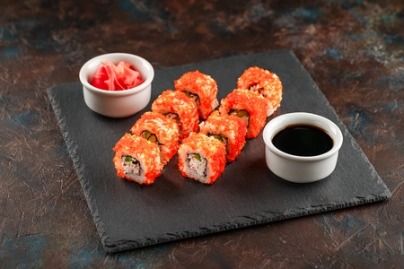 Photo pour Japanese sushi rolls served on stone slate on dark background. Sushi rolls, maki, pickled ginger and soy sauce. Sushi background. Asian or Japanese food - image libre de droit