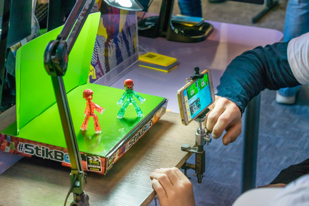 Photo pour KROPIVNITSKIY, UKRAINE – 12 MAY, 2018: Stop motion animation process with Stikbot details and toy figures. Boy expose stop motion elements to create animations using smartphone - image libre de droit