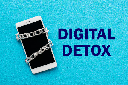 Photo pour White smartphone with metal chain on blue background. Digital detox, dependency on tech, no gadget and devices concept - image libre de droit