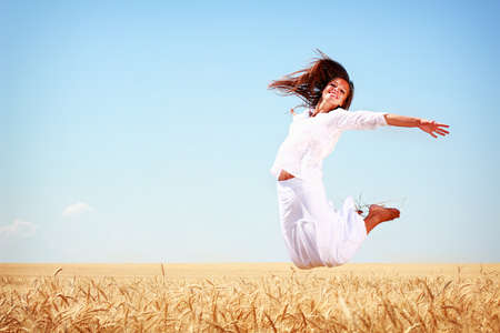 Photo for Happy young woman jumping in golden wheat field - Royalty Free Image