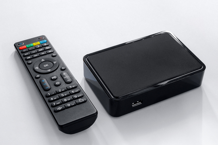 Foto de Iptv box and remote controller. Modern multimedia device for viewing television via the Internet, multimedia player and control panel. - Imagen libre de derechos
