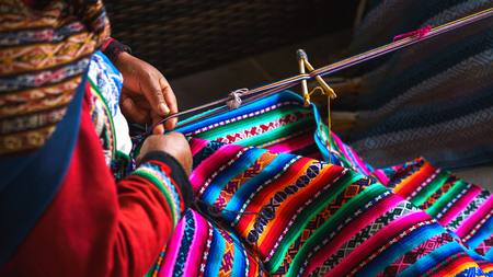 Photo for Hands of peruvian woman making alpaca wool carpet with national pattern close-up. Manufacture of wool material in Peru, Cusco. Woman dressed in colorful traditional native Peruvian closing - Royalty Free Image