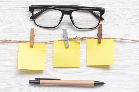 Photo pour Blank paper stickers with copy space on a clothespin on a rope and eye glasses on a white table background. To do list. - image libre de droit