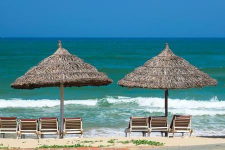 Foto de Beach umbrellas and deck chairs in front of the My Khe beach in Da Nang, Vietnam. - Imagen libre de derechos