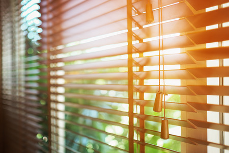 Photo pour Wooden blinds with sun rays. - image libre de droit