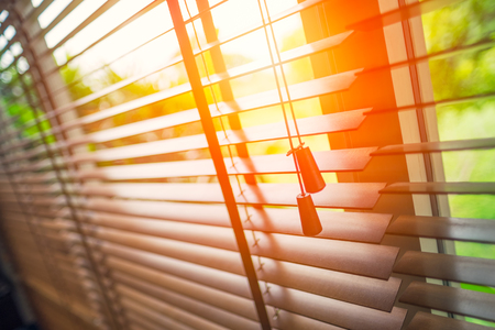 Photo pour Wooden blinds with sun light. - image libre de droit