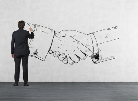 Photo for businessman in room drawing handshake on wall - Royalty Free Image