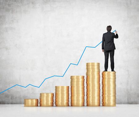 Photo pour businessman drawing chart standing on gold coins - image libre de droit
