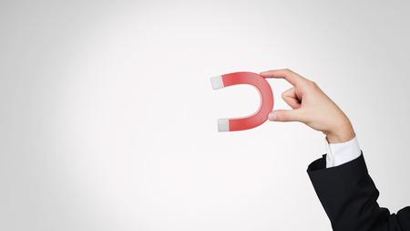 Foto de hand holding large red magnet, close up - Imagen libre de derechos