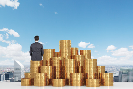 Photo pour businessman sitting on gold coins on table and looking to city - image libre de droit