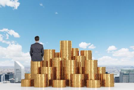 Foto de businessman sitting on gold coins on table and looking to city - Imagen libre de derechos