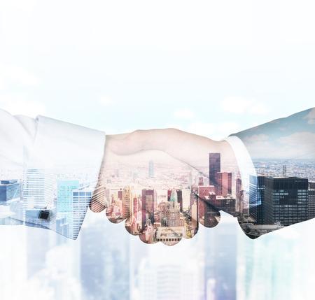 Photo pour handshake on a building background, double exposure - image libre de droit