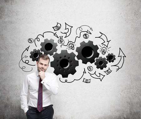 Foto de Young businessman is thinking about optimisation of the business process. - Imagen libre de derechos