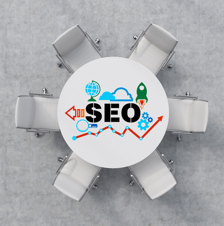 Foto de Top View of a conference room. A white round table and six white chairs around. Colourful SEO flowchart is drawn on the table surface. Office interior. 3D rendering. - Imagen libre de derechos