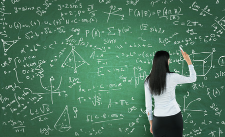 Photo pour Rear view of a thoughtful woman who is writing math calculations on green chalk board. - image libre de droit