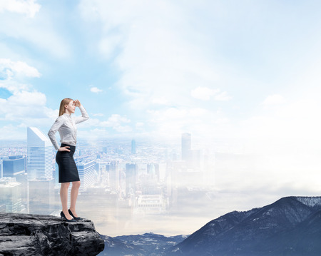 Photo pour Business woman standing on a rock and looking at the flying business city. Illusion of the panoramic view of New York. - image libre de droit