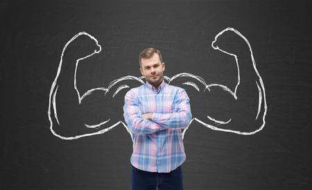 Foto de Young handsome man in casual shirt with drawn powerful hands. Black chalkboard background. - Imagen libre de derechos