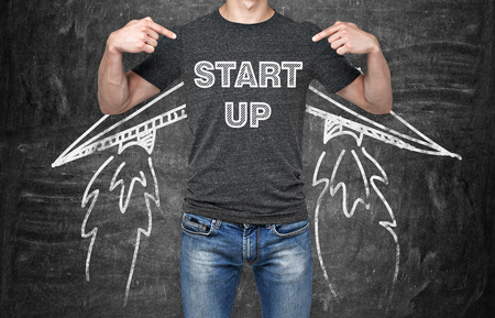 Foto de A businessman is pointing out in the chest where is a word collocation ' start up '. A concept of the starting up new business. Drawn wings. Black chalk board on the background. - Imagen libre de derechos