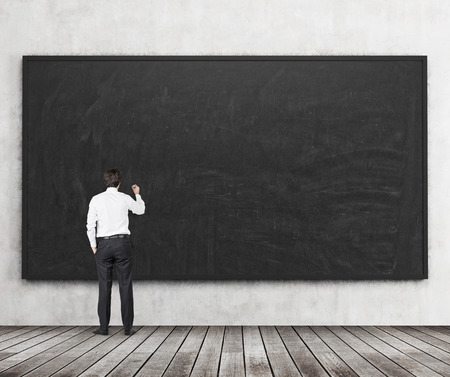 Photo pour Rear view of the man who is going to write something on the black chalkboard. Wooden floor and concrete wall. A concept of the beginning of new academic year. A class room. - image libre de droit