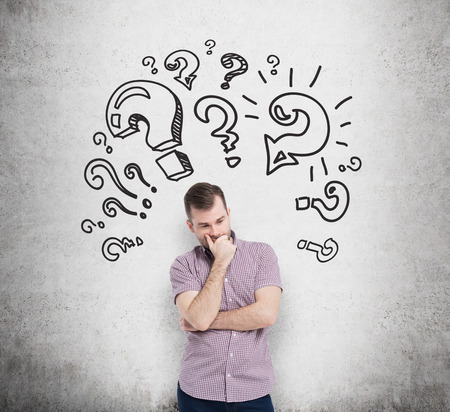 Foto de Young man in casual shirt holds his chin and thinks about unsolved problems. Question marks are drawn around the head. Concrete wall on the background. - Imagen libre de derechos
