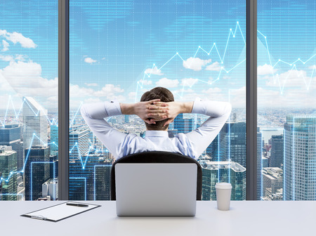 Photo for Rear view of the relaxing businessman with crossed hands behind his head, who is looking at NYC. Modern Panoramic office or work place with New York city view. Financial charts are over the windows. - Royalty Free Image