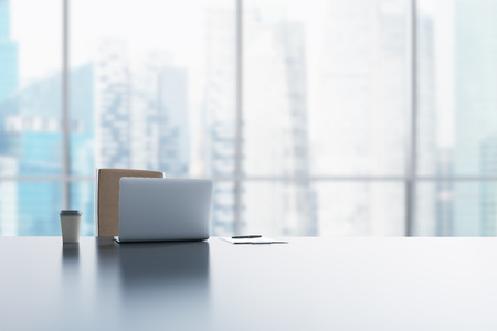 Photo for A workplace in a modern panoramic office in Singapore. A laptop, notepad and a coffee cup are on the white table. 3D rendering. - Royalty Free Image