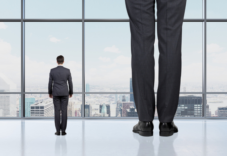 Photo for Rear view of two professionals in formal suites who stand in front of panoramic window with New York city view. The concept of professional consulting services. - Royalty Free Image