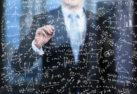 Photo pour A business person is writing down math formulas on the glass screen in the evening modern panoramic office. - image libre de droit